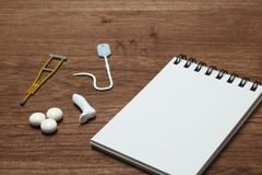 Miniature items of illness or injury beside memo pad. Stock Images