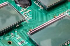 Miniature LCD panels on the motherboard. Circuit Board close-up. Detail of an electronic printed circuit board with mounted display screen Royalty Free Stock Image