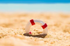 Miniature Lifebuoy In Sand. Miniature White And Red Lifebuoy In Sand At Beach Stock Photo