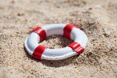 Miniature lifebuoy on sand Stock Photos