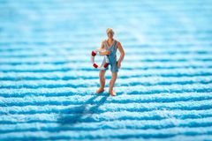 Miniature lifeguard carrying a life ring. Or preserver as he crosses a blue ridged textile conceptual of the sea royalty free stock image