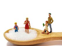 Miniature little children standing on a wooden spoon and thinking of sugar, diet, fat and diabetes. Health care concept. Miniature little children standing on a stock photos