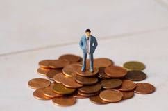 Miniature little people, man posing over a pile of one cents in a white background Stock Image