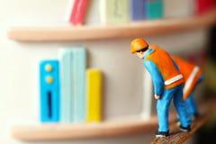 Figure model scene. Miniature maintenance plastic figure model in action of inspection book symbol Royalty Free Stock Photo