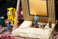 Miniature Maintenance Team. A team of miniature toy figurines busy with repair and maintenance Stock Photo