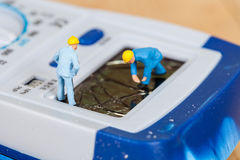 miniature maintenance team repairing a broken  multimeter Stock Image