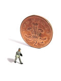 Miniature man and british coin Stock Image