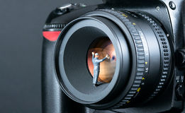 Miniature man cleaning camera lens Royalty Free Stock Image