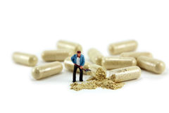 Miniature man digging medicine. Concept macro image of a man digging through some spilled medication out of a capsule. It can symbolize a drug addiction, digging stock photo