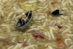 Miniature man fishing in soup Royalty Free Stock Photo
