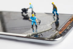 The miniature man fixing broken smartphone. Close up shot royalty free stock photo