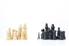 Miniature man inbetween competing teams mediation or competition Royalty Free Stock Photos