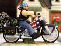 Miniature Man on a Motorcycle. Miniature holiday village figurine of a man on a motorcycle Stock Photos