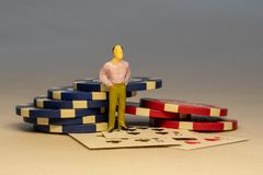 Miniature man standing next to bunch of chips some cards in the background. Casino and gambling concepts stock photos