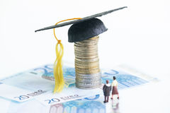 Miniature man and woman standing on top of 20 Euro banknotes looking at the Mortarboard. Education savings with miniature man and woman standing on top of 20 Royalty Free Stock Images