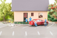 Miniature mechanic changing a punctured tyre. Close up stock photos