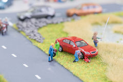 Miniature mechanics replacing a flat tyre at the roadside Stock Photos