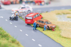 Miniature mechanics replacing a tyre off the roadway. Close-up Royalty Free Stock Images