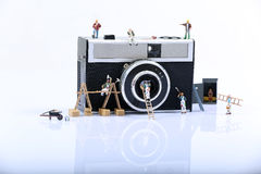 Miniature men working. On a huge photo camera Stock Images