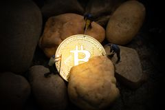 Miniature miners digging golden bitcoin in mine stock photography
