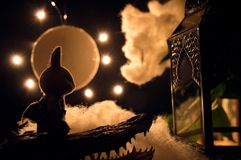 Miniature model of bunny standing on monster in moonlit dreamscape. Moon, clouds and stars in background. Bunny approaching a structure royalty free stock images