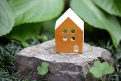 Miniature  model of house on stone. In the garden Stock Photography