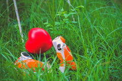 Miniature motorcycle carrying a red heart cushion on the grass Royalty Free Stock Images