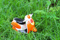 Miniature motorcycle carrying a red heart cushion on the grass Royalty Free Stock Image