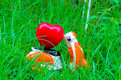 Miniature motorcycle carrying a red heart cushion on the grass Royalty Free Stock Photo