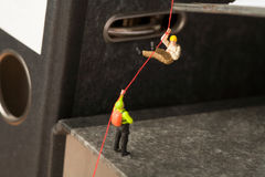 Miniature Mountaineers Climbing Office Files. Miniature models of mountaineers rope climbing up a set of randomly positioned files Stock Photo