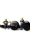 Miniature musicians earphones stock image