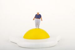 Miniature of an obese man and fried egg Stock Photography