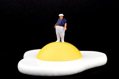 Miniature of an obese man and fried egg Royalty Free Stock Image