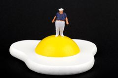 Miniature of an obese man and fried egg Stock Photo