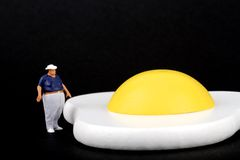 Miniature of an obese man and fried egg Royalty Free Stock Images