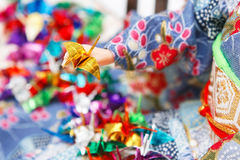 Miniature origami birds and a Japanese doll. Dressed in kimono. Shallow depth of field. Focus on the golden bird Royalty Free Stock Photography