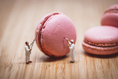 Miniature painters coloring macaroon. Color tone tuned. Royalty Free Stock Photo