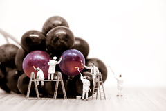 Miniature painters coloring red grapes. Macro photo royalty free stock photo