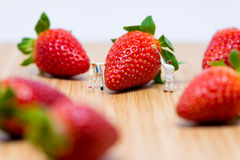 Miniature painters coloring strawberry. royalty free stock image