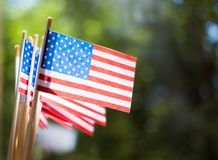Miniature paper flags USA. American Flag on rustic wooden background. Miniature paper flags USA. American Flag on blurred background outdoors stock photography