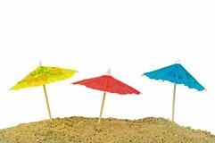 Miniature paper sun umbrellas in sand Stock Images