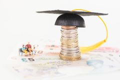 Miniature parents saving for their child`s education fund. Miniature parents and their child besides the mortarboard on top of stacked of coins and banknotes royalty free stock images