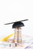 Miniature parents and their children looking at th. E mortarboard on top of British coins and Pounds sterling banknotes Stock Images