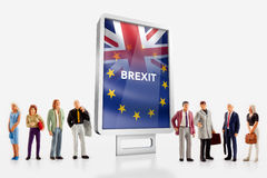 Miniature people – people in front a billboard with United Kingdom and European union flags combined for the 2016 referendum Royalty Free Stock Photography