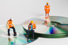 Miniature people in action with CDs Royalty Free Stock Image