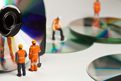 Miniature people in action with CDs Stock Photography