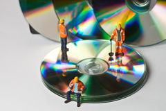 Miniature people in action with CDs Royalty Free Stock Photo