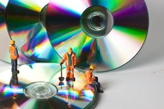 Miniature people in action with CDs Stock Image