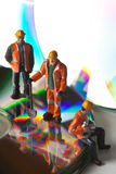 Miniature people in action with CDs Stock Images