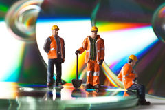 Miniature people in action with CDs Royalty Free Stock Images